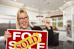 Young Woman Holding Sold Sign and Keys Inside New Kitchen. Happy Young Woman Holding Sold For Sale Real Estate Sign and Keys Inside Beautiful Custom Kitchen Royalty Free Stock Photo