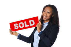 Young Woman Holding Sold Sign. Portrait of African American businesswoman holding sold sign isolated over white background Stock Photography