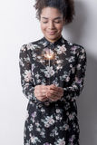 Young woman holding sparkler in her hands. And smiling near white wall royalty free stock images