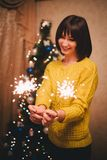 Young woman holding sparkles in her hands near christmas tree Royalty Free Stock Photos