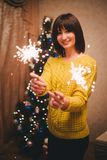 Young woman holding sparkles in her hands near christmas tree Stock Photo