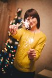 Young woman holding sparkles in her hands near christmas tree Stock Photography