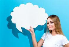 Young woman holding a speech bubble. On a blue background royalty free stock photo