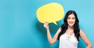 Young woman holding a speech bubble. On a solid background Royalty Free Stock Photo
