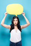 Young woman holding a speech bubble Royalty Free Stock Photos