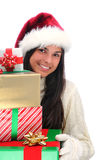 Young Woman holding stack of Christmas Presents. Young woman wearing a Santa Claus hat holding a large stack of assorted Christmas presents. Vertical format Royalty Free Stock Photo