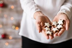 Young woman holding star shaped Christmas cookies. Unrecognizable young woman holding decorated star-shaped cookies. Christmas time Stock Photo
