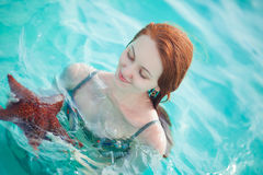 Young woman holding a starfish royalty free stock photo