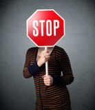 Young woman holding a stop sign Stock Images