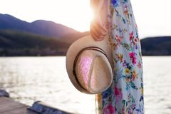 Young woman holding straw hat on wooden pier near to lake. Stock Image