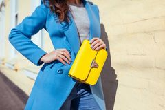Young woman holding stylish handbag and wearing trendy blue coat. Spring female clothes and accessories. Fashion. Young woman holding stylish yellow handbag and stock photo