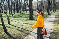 Young woman holding stylish handbag and wearing yellow sweater. Spring female clothes and accessories. Fashion stock images