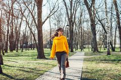 Young woman holding stylish handbag and wearing yellow sweater. Spring female clothes and accessories. Fashion stock image