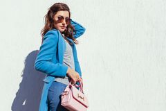 Young woman holding stylish handbag and wearing trendy blue coat. Spring female clothes and accessories. Fashion royalty free stock photography