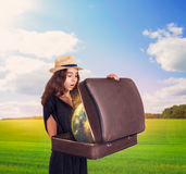 Young woman holding a suitcase with magic globe. Royalty Free Stock Images