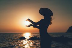 Young Woman Holding Sun In Sunset stock photography