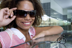 Young woman holding sunglasses on face, smiling, close-up Stock Photo