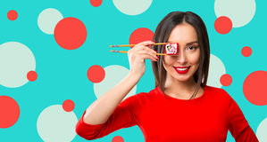Young woman holding sushi with a chopsticks, isolated on blue Royalty Free Stock Photos