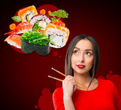 Young woman holding sushi with a chopsticks, isolated on red Stock Photos