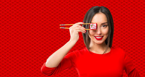Young woman holding sushi with a chopsticks Stock Photo