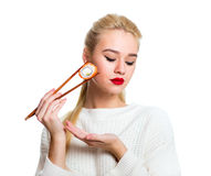 Young woman holding sushi with a chopsticks, isolated on white Stock Images