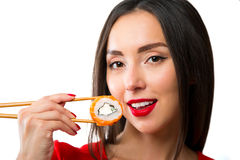 Young woman holding sushi with a chopsticks, isolated on white Royalty Free Stock Photo