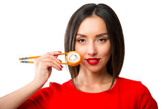 Young woman holding sushi with a chopsticks, isolated on white Stock Photo
