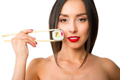 Young woman holding sushi with a chopsticks, isolated on white Royalty Free Stock Images