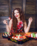 Young woman holding sushi with a chopsticks. Woman with perfect make up holding sushi roll. Royalty Free Stock Images