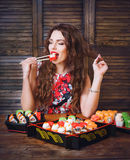 Young woman holding sushi with a chopsticks. Woman with perfect make up holding sushi roll. Royalty Free Stock Photography
