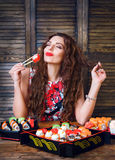 Young woman holding sushi with a chopsticks. Woman with perfect make up holding sushi roll. Stock Images