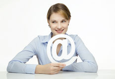 Young woman holding an @ symbol. In her hands Royalty Free Stock Image