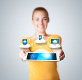 Young woman holding tablet with modern devices. Young woman holding tablet with abstract clouds and modern devices Royalty Free Stock Image
