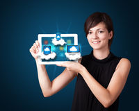 Young woman holding tablet. Beautiful young woman holding tablet with modern devices in clouds Stock Photography
