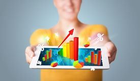 Young woman holding tablet with colorful graphs and diagrams Stock Photos