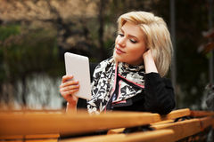 Young fashion woman using a tablet computer outdoor Royalty Free Stock Photo