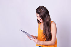 Young woman holding tablet computer isolated on grey background. Tablet computer. Young woman holding tablet computer isolated on grey background. Casual Royalty Free Stock Photography