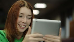 Young woman holding a tablet computer, looking at screen and smiling, saying something. stock video