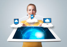 Young woman holding tablet with modern devices. Young woman holding tablet with abstract clouds and modern devices Stock Photos