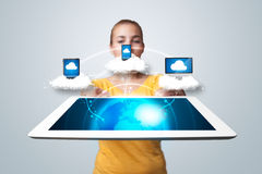 Young woman holding tablet with modern devices. Young woman holding tablet with abstract clouds and modern devices Royalty Free Stock Photos