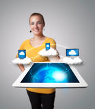 Young woman holding tablet with modern devices. Young woman holding tablet with abstract clouds and modern devices Royalty Free Stock Images