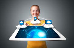 Young woman holding tablet with modern devices. Young woman holding tablet with abstract clouds and modern devices Stock Image