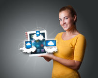 Young woman holding tablet with modern devices. Beautiful young woman holding tablet with modern devices in clouds Stock Photography