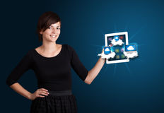 Young woman holding tablet with modern devices in clouds. Beautiful young woman holding tablet with modern devices in clouds Stock Photo