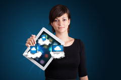 Young woman holding tablet with modern devices in clouds. Beautiful young woman holding tablet with modern devices in clouds Royalty Free Stock Photography