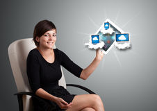 Young woman holding tablet with modern devices in clouds. Beautiful young woman holding tablet with modern devices in clouds Stock Image