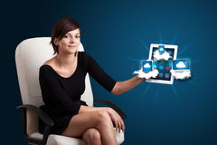 Young woman holding tablet with modern devices in clouds. Beautiful young woman holding tablet with modern devices in clouds Stock Images