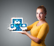 Young woman holding tablet with modern devices in clouds Stock Photography