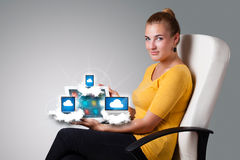 Young woman holding tablet with modern devices in clouds. Beautiful young woman holding tablet with modern devices in clouds Royalty Free Stock Image