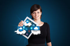 Young woman holding tablet with modern devices in clouds. Beautiful young woman holding tablet with modern devices in clouds Royalty Free Stock Photos